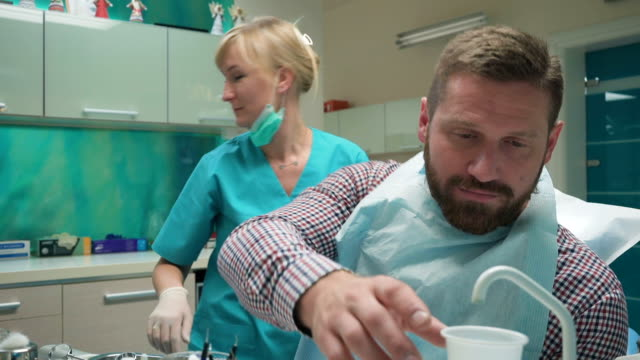 Patient rinsing teeth and looking for camera after dental examination. video