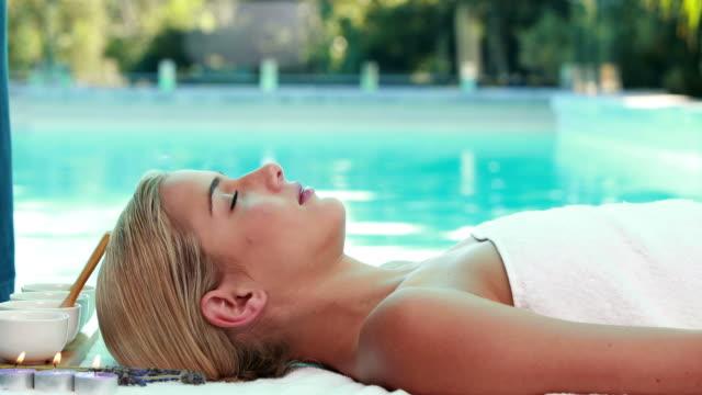 Peaceful blonde lying on massage table poolside video
