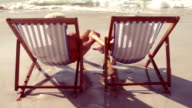 Peaceful senior couple holding hands in beach chair video