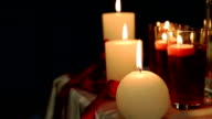 Peaceful valentine candles light for dinner on table decorated with tablecloth and red tapes at night video