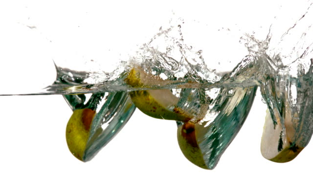 Pear segments plunging into water on white background video
