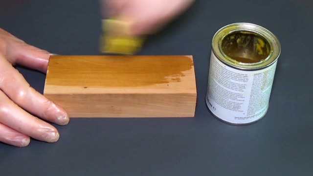 Pear wood. The bar of solid wood is covered with stain. The girl covers a bar of rare wood with lacquer. The joinery impregnates the wood with wax. Gray background video