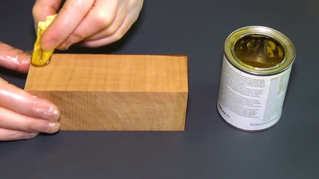 Pear wood. The bar of solid wood is covered with stain. The girl covers a bar of rare wood with lacquer. The joinery impregnates the wood with wax. Gray background. The end part of the wooden board video