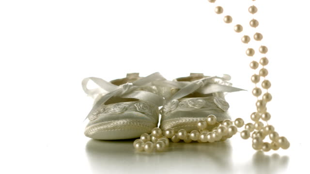 Pearl necklace falling onto baby shoes video