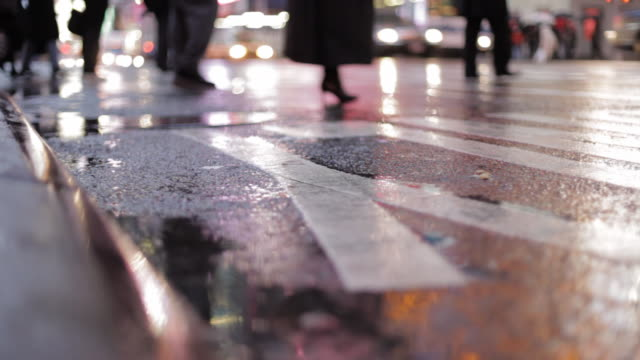 pedestrian and vehicle traffic in the rain   curb-level view video