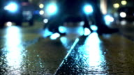 Pedestrians and falling snow on wet crosswalk in winter. Snowflakes in headlight video
