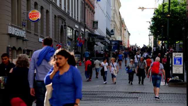 Pedestrians crowd a busy street in Oslo, Norway video