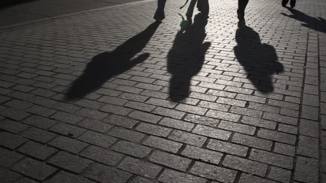 Pedestrians silhouetted by late sun - looping video