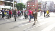 pedestrians walking through crosswalk in modern street of guangzhou,time lapse video