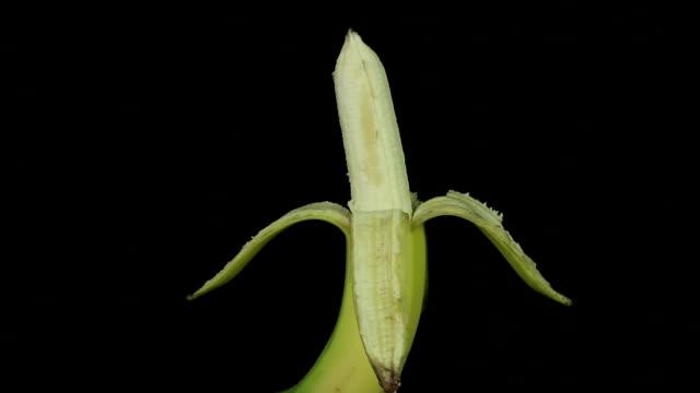 Peeled banana rotates on a black background loop video