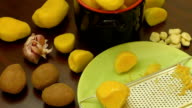 Peeled new potatoes in bowl on wooden table video