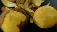 Peeled potatoes and potato peel on the black background video