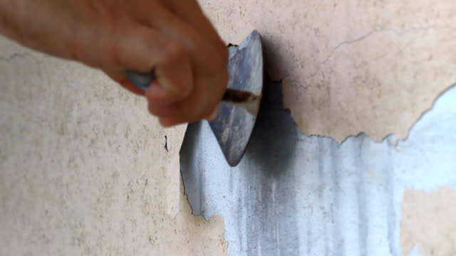 Peeling a paint on an old house wall. video