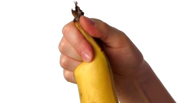Peeling banana on white, slow motion, close up video