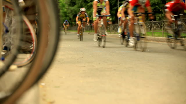 Peloton of bike racers passes the camera video