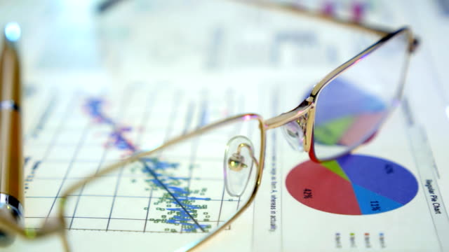 Pen and glasses lie on the documents with diagrams and graphs video