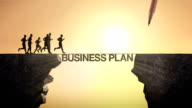 Pencil write 'Business plan', connecting the cliff. Businessman crossing the cliff. video
