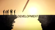 Pencil write 'DEVELOPMENT', connecting the cliff. Businessman crossing the cliff. video
