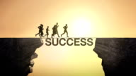 Pencil write 'SUCCESS', connecting the cliff. Businessman crossing the cliff. video