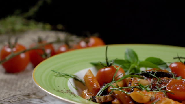Penne pasta with cherry tomatoes, aubergines, decorated witrh basil leaves in a deep plate with a green border. Close-up. Slow motion. video