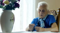 pensive and depressed Elderly woman praying with rosary beads video
