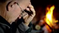 pensive man near the fire: fireplace, wood, flames video