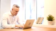 Pensive Middle Age Man Working on Laptop in Office video