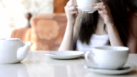 Pensive, thoughtful beautiful woman drinking coffee in cafe video