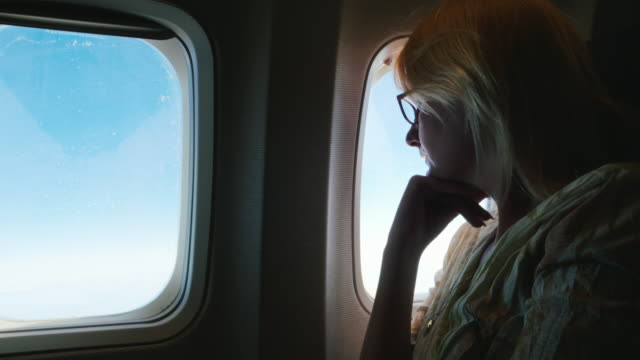 A pensive woman flies in an airplane, looks out the window. Side view, silhouette video