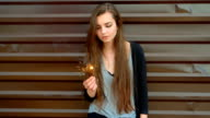 Pensive woman holding sparkler in her hands on the street in front of brown wall, slow-motion shot, retro color video
