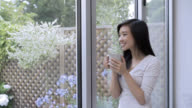 Pensive woman looking out the window drinking a cup of coffee video