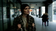 Pensive young fashion woman with backpack walking in the city, steadicam shot video