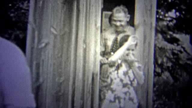 OKLAHOMA, USA - 1943: People comedically leaving a stinky outhouse. video