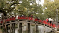 people cross a red bridge that leads them video