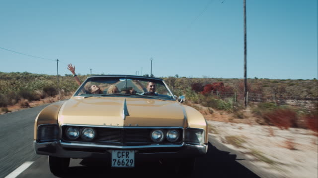 People driving in retro car on outback road video