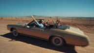 People driving in retro car over dirt road video