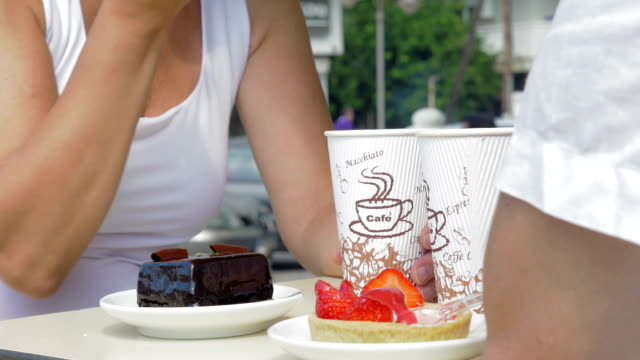 People eating desserts and drinking coffee in cafe video