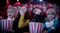 People eating popcorn and grimacing at cinema video