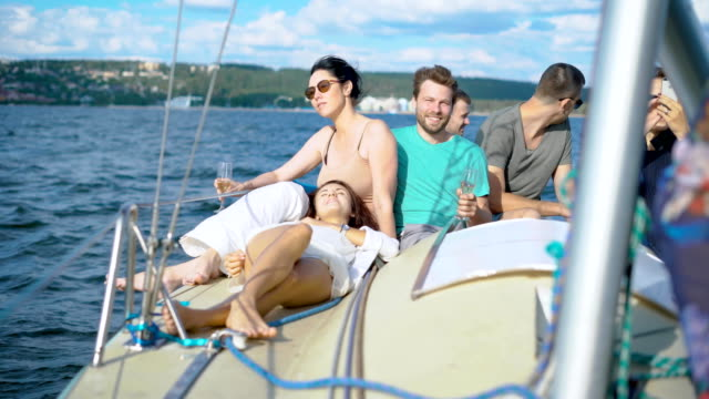 People enjoying champagne and each other on yacht during party video