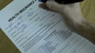 CNGLMED545 - People filling out generic healthcare insurance forms. video