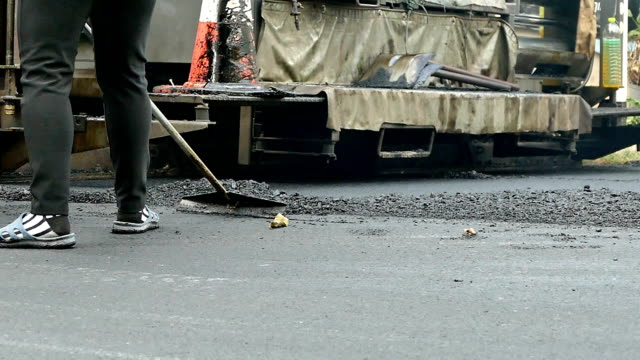 People filling the hole on the street. Road roller flattens asphalt. video