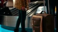 People getting luggage on conveyer belt video