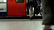 People getting on a London Underground tube train which then moves off. video