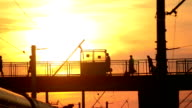 People go on the bridge, pass over the bridge railroad tracks at sunset, black silhouettes, handbags, luggage video