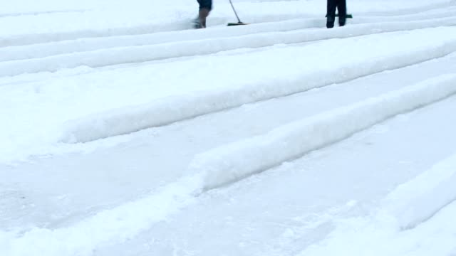 People have fun on ice hills in park. video