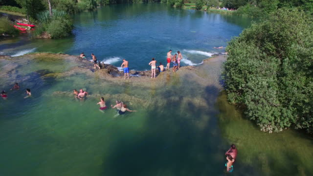 People having a good time and enjoying sunny day at river video