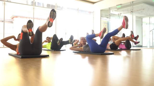 People in class doing bicycle crunche video