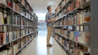 DS People in public library searching for books on shelves video