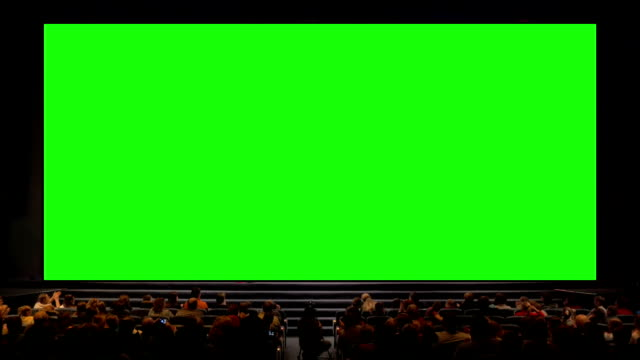 People in the auditorium with chroma key screen video
