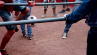 People kicking a ball in the foosball way video